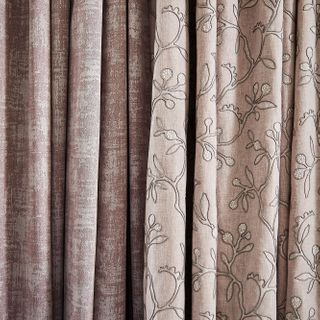 Close up of neutral beige featuring delicate embroidery curtains and  textured shimmering purple curtains