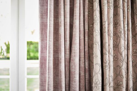 close up of neutral beige featuring delicate embroidery curtains and  textured shimmering purple curtains hanging on doors