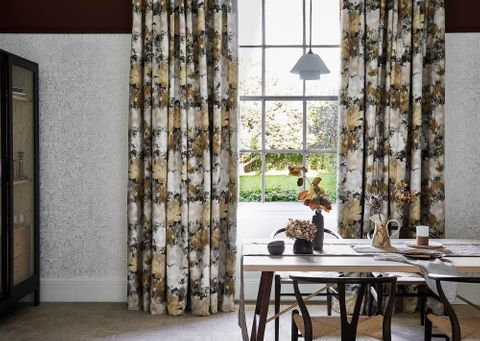 Dining room with floral print velvet curtains