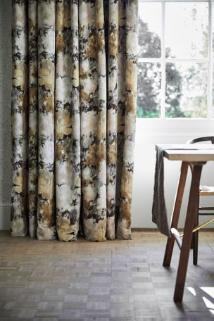Close up detail of painterly floral velvet curtains at a single window