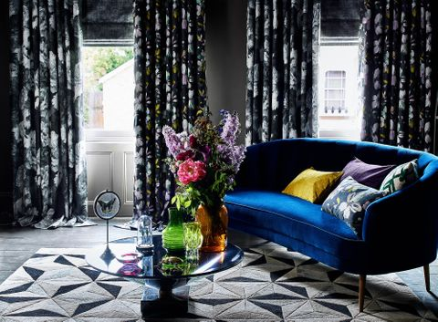 Windows in living room dressed with charcoal Roman blind under a floral print curtain