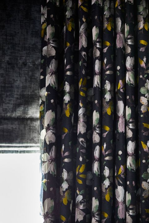 A close up of a charcoal Roman blind under a floral print curtain