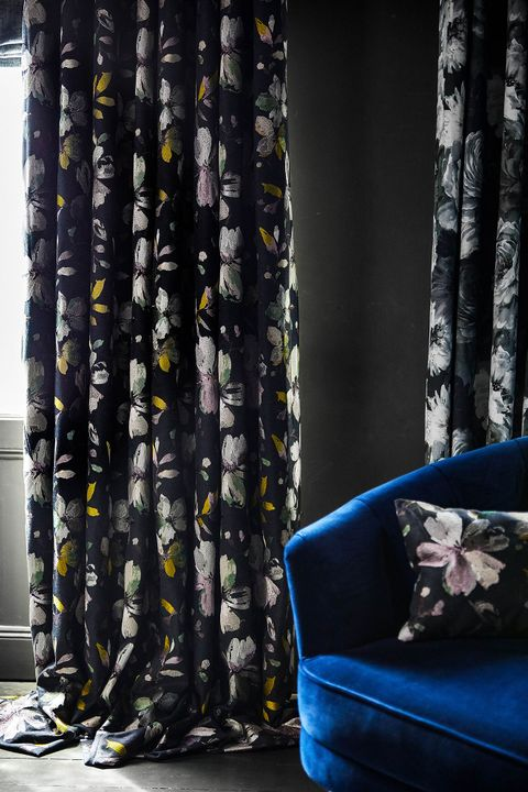 Close of up dark floral curtains in a living room. Matching floral print cushion have been placed on blue sofa