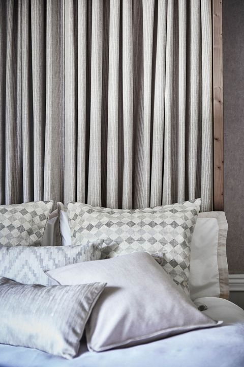 View of bed with grey striped curtain headboard covered with plain, printed and patterned cushions