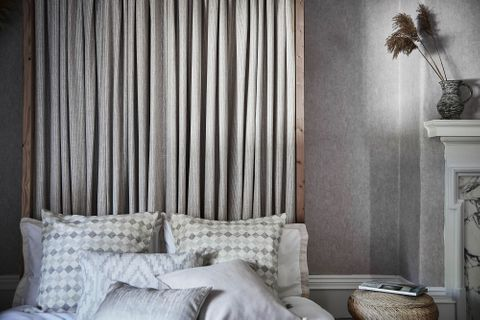 Grey striped curtains on a bed headboard and few patterned, plain and geometric print cushions have been placed nicely on bed