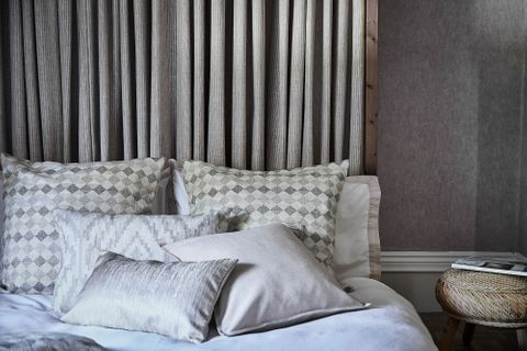 View of bed with grey striped curtains headboard covered with plain, printed and patterned cushions