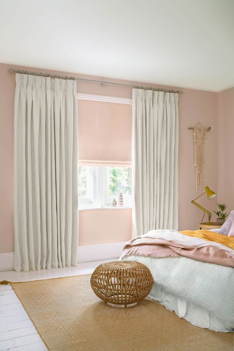 Full length cream embroidered curtains over pink Roman blinds hanging over window in bedroom