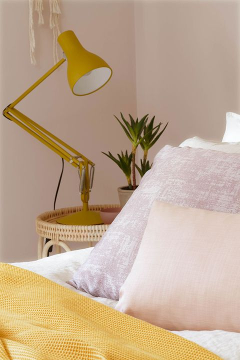 View of bed covered with mustard shrug and cushions of cream and light pink color by mustard lamp