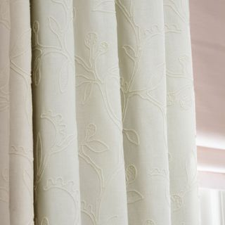 Close up of cream embroidered curtains and pink roman blinds in a bedroom