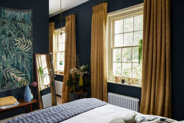 A dark blue bedroom with two windows dressed in gold coloured curtains