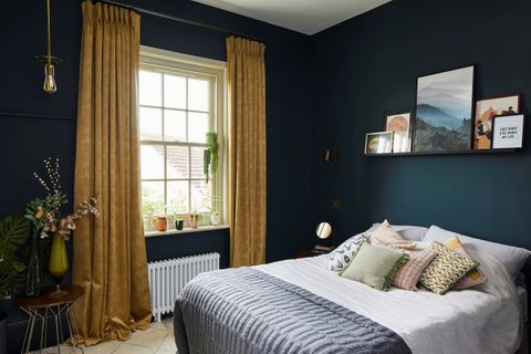 A navy blue bedroom with a window dressed with gold curtains