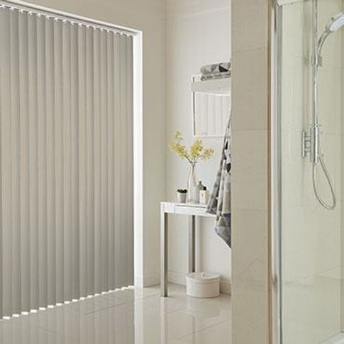 Grey vertical blinds fitted to a wide window in a bathroom decorated in white