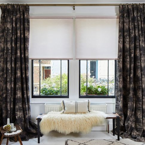 A white bedroom with two black sash windows dressing with dark curtains and light pink Roller blinds