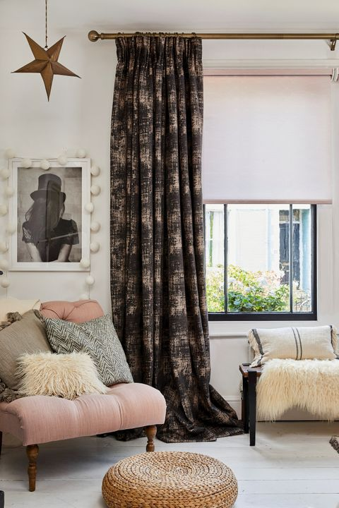 A black framed window with a textured grey curtain and pink Roller blind