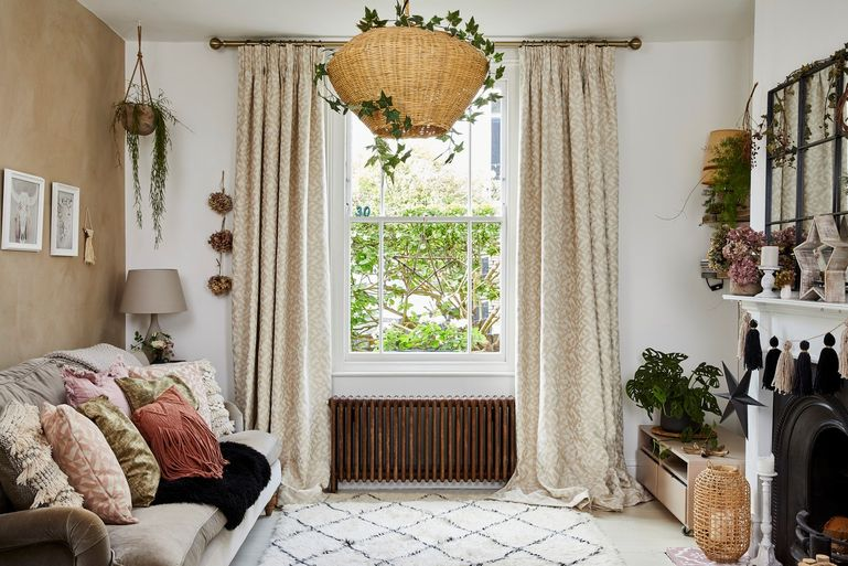 A living room with a single sash window dressed with beige coloured curtains