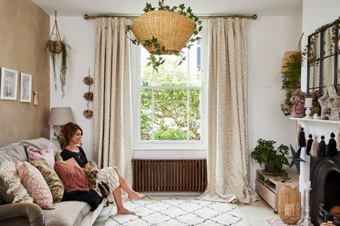 A woman sat in a white and honey-coloured living room with a single sash windows dressed with cream and white patterned curtains