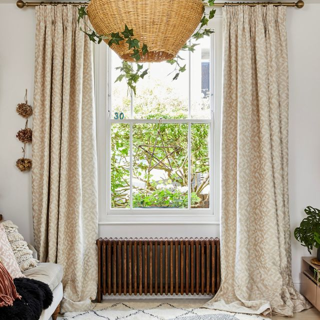 A single sash window with a rust-coloured radiator underneath, dressed in cream curtains