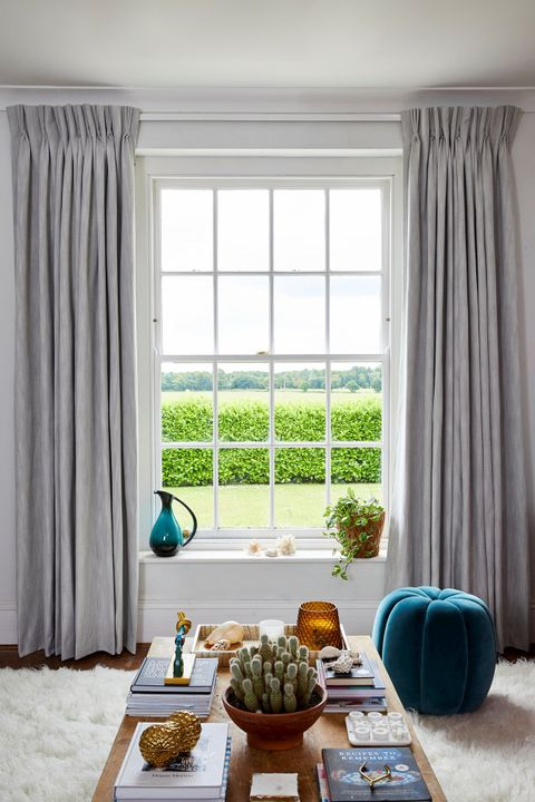 A single sash window dressed with light grey curtains