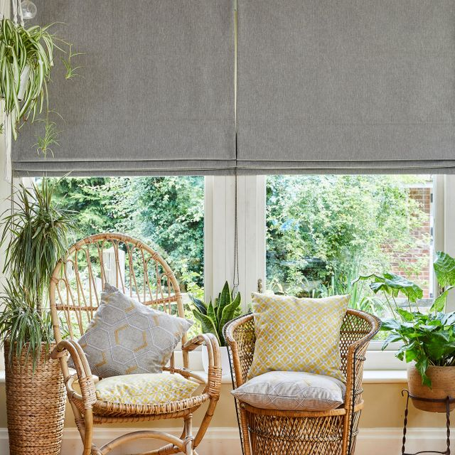 A conservatory with two wicker chairs