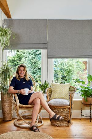A woman sat holding a cup on a wicker chair in a conservatory