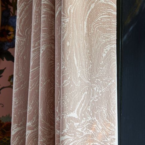 A close up shot of pink curtains featuring a subtle marble print