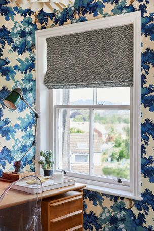 A window above a vintage writing desk dressed with a blue patterned Roman blind
