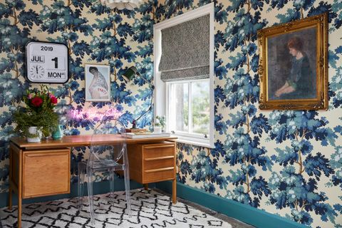 An office space with blue and white patterned wallpaper and a vintage writing desk