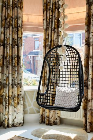 Hanging chair  in front of bay window dressed with floral velvet curtains