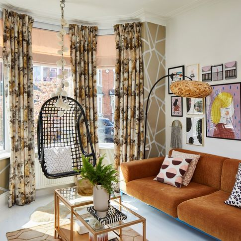 Maximalist living room with velvet curtains and Roman blinds at a bay window
