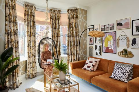 A woman sat in a 70s style living room with floral curtains