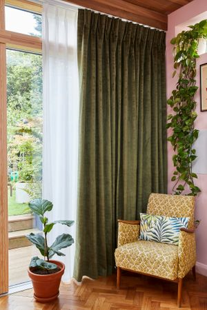 A floor to ceiling window with dark green curtains and a white Voile