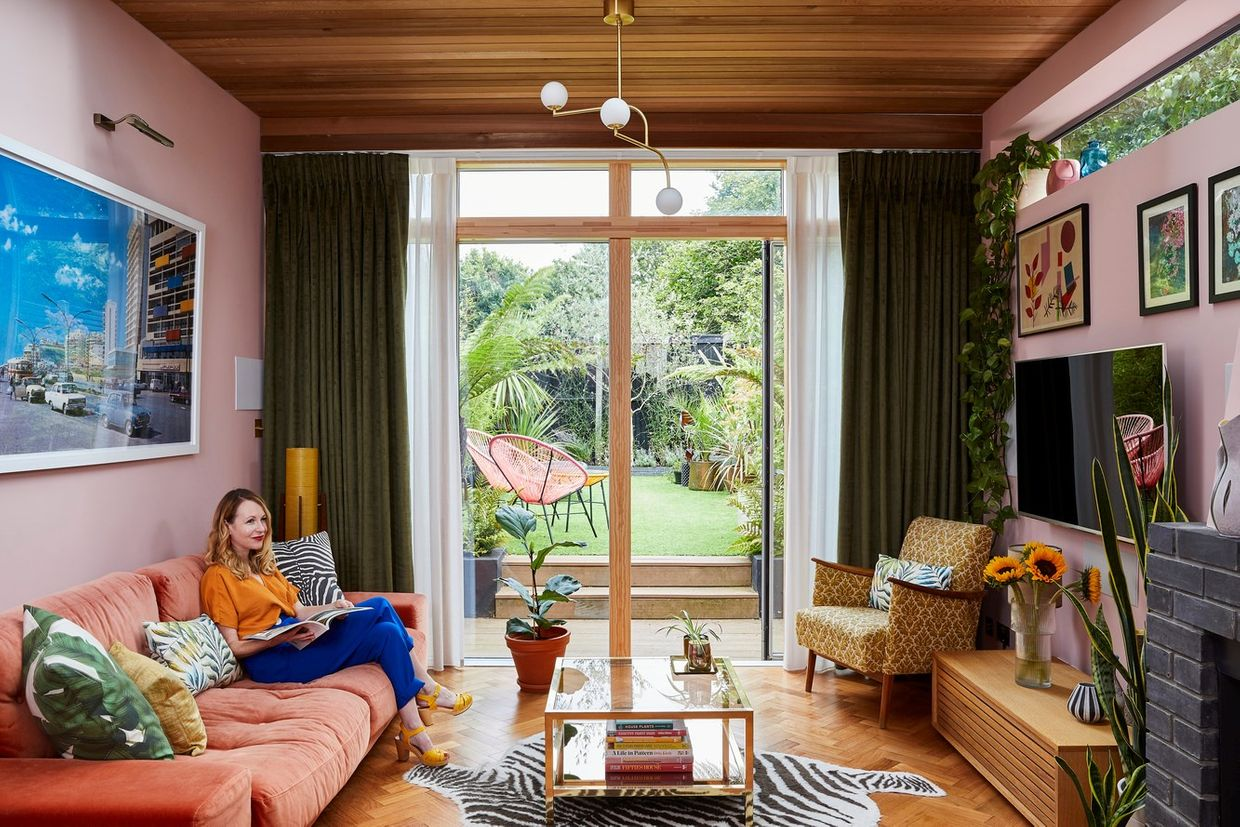 A lady sat on a sofa in a pink, 70s style living room.