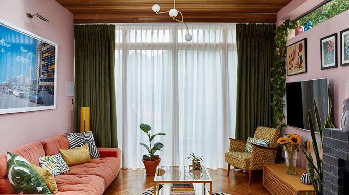 A pink, 70s style living room with wood panelled ceiling and floor