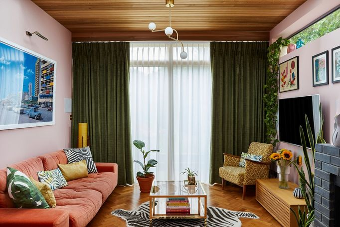 A pink 70s style living room with green curtains