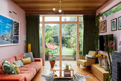 A pink 70s style living room with large glass doors that look out onto a garden.