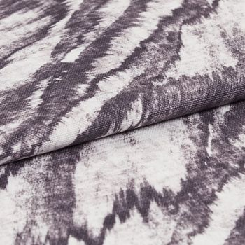 Purple and white patterned drift storm swatch on a ream of fabric