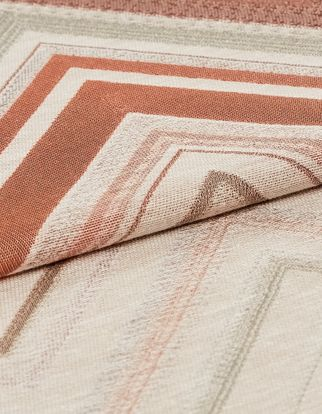 Repeating shades of blush and pink in different thicknesses are patterned on white material
