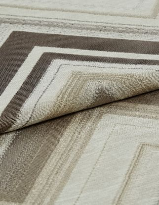 Folded fabric that has a white base colour while the rest of the fabric is patterned with rectangular outlines in brown and beige colours