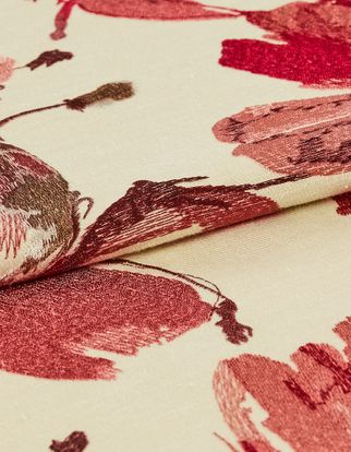 Floral designs in red with dark hand woven shades for a watercolour like style on cream coloured material