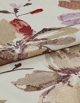 Flowers and twigs decorate the white coloured fabric in a variety of colours in a style that looks hand stitched
