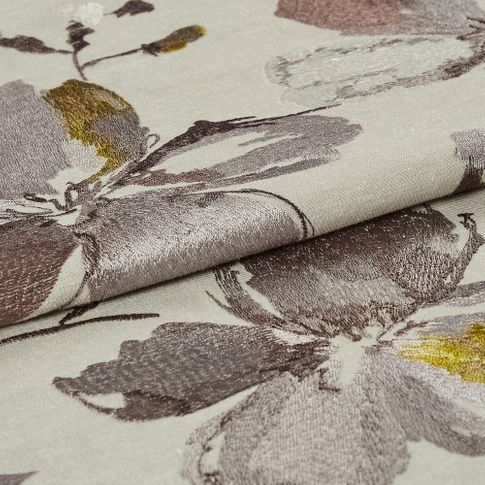 Beige coloured fabric with a flowers in a watercolour style that pattern the fabric