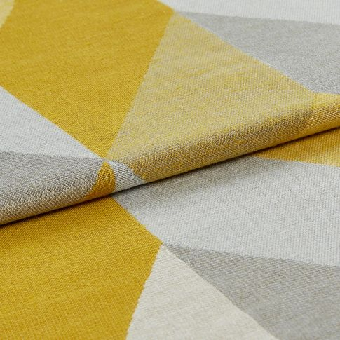 Folded fabric in shades of yellow, grey and white that are arranged in a repeating geometric pattern