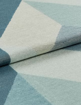 Material patterned with a repeating geometric design in shades of dark blue, light blue and white