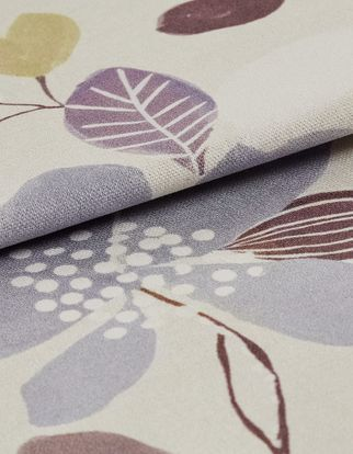 Neutral coloured fabric decorated with flowers and leaves in a variety of colours that repeats throughout the material
