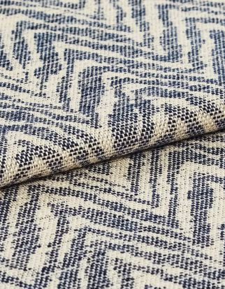 Repeating wave like pattern of blue on beige coloured fabric