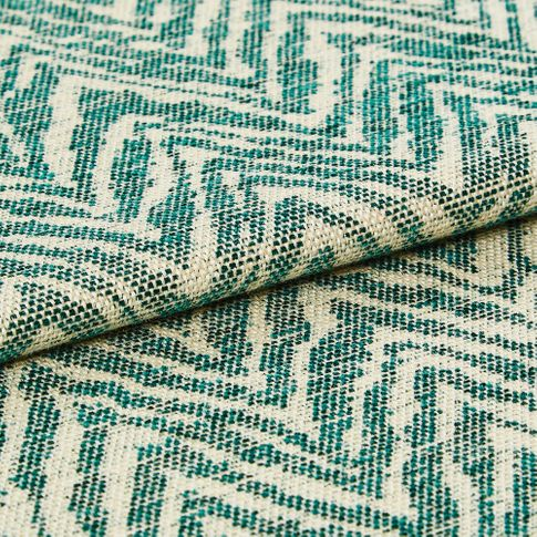 Wave like pattern in teal on folded beige coloured fabric