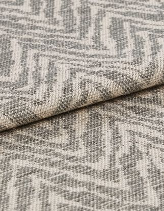 Beige coloured folded fabric that is decorated with a repeating wave like pattern in light grey