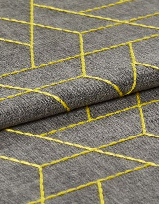 Yellow lined geometric shaped in a repeating triangular pattern are woven into this swatch on the grey base colour of the fabric