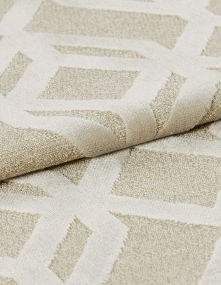 Cream coloured fabric with a repeating geometric pattern in white