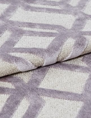 Soft white fabric that has a mauve coloured geometric style which repeats throughout the material
